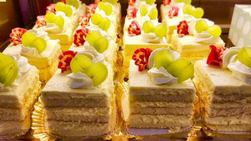 Kuvassa viipaloituja voileipäkakkuja, joiden päällä herkullisia koristeita.